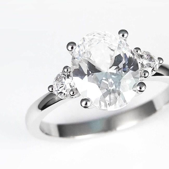 prstan z ovalnim kamnov in dvema stranskima povečava
