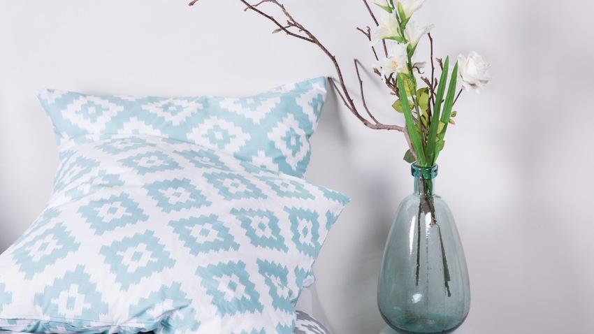 Zwei gemusterte Kissen mit einer Blumenvase