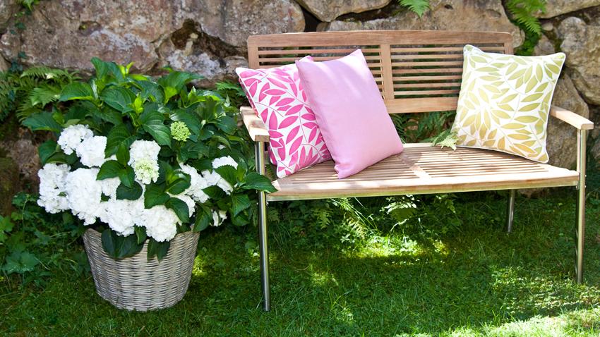 Frühlingsdeko mit bunten Kissen für den Garten