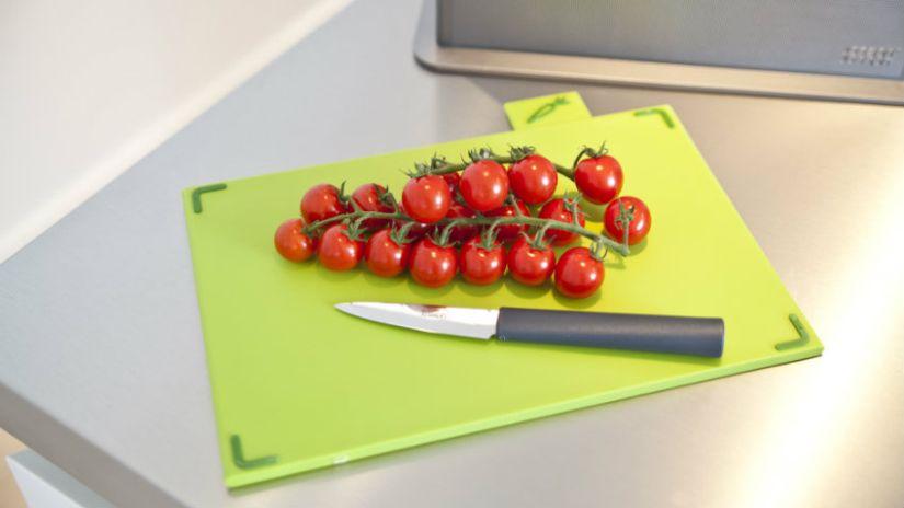 Planche à découper en plastique vert et tomates cerises