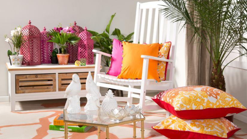Coussins orange posés sur une chaise de jardin blanche