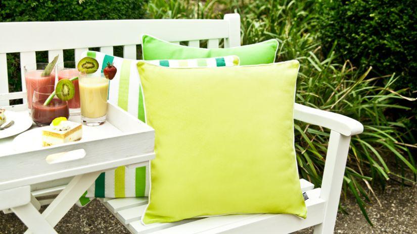 Coussins verts sur banc de jardin blanc