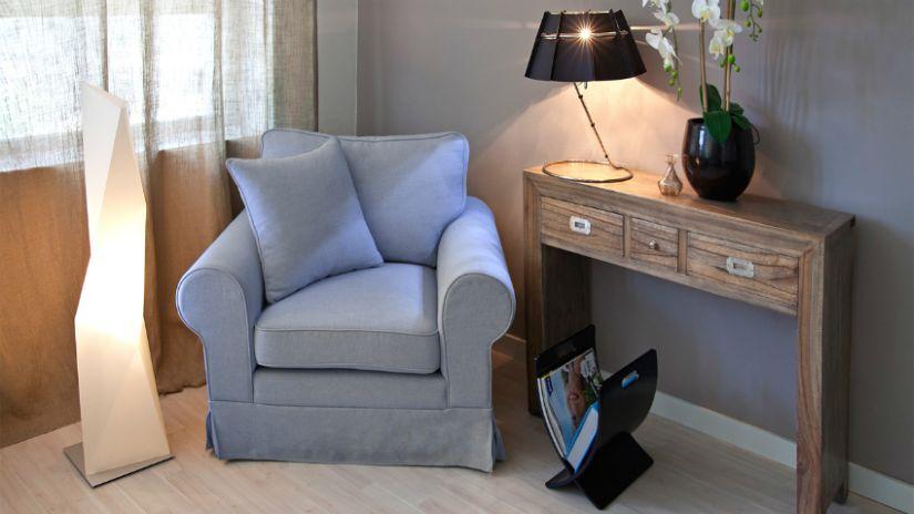 Fauteuil gris et console dans un salon