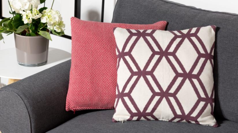Coussin carré bordeaux sur un canapé