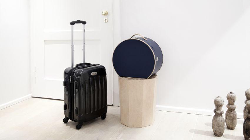 Valise rigide noire dans un hall d'entrée
