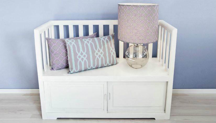 cassapanca in legno con schienale bianca cuscini lilla lampada