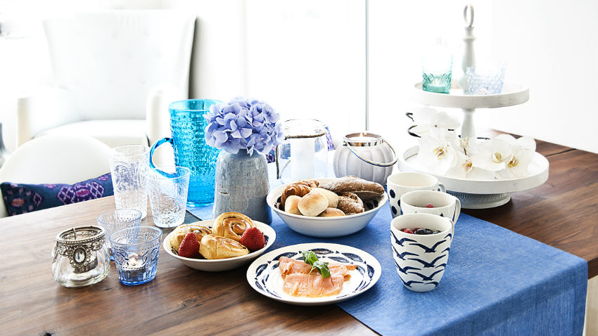 runner in lino alzata tazze piatti fiori vasi tavolo in legno