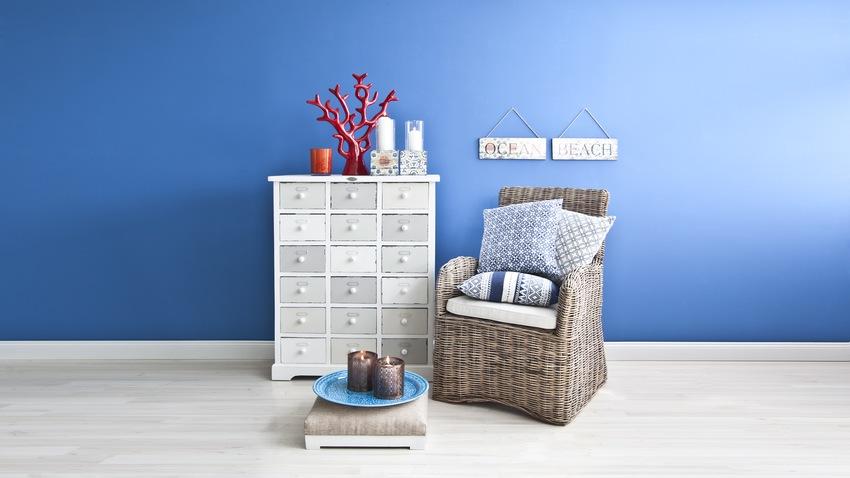 rotan stoel en passende kast zeeblauwe muur