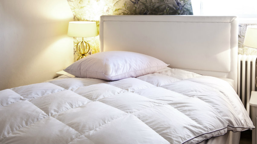 wit bed met wit hoofdbord en dekbed