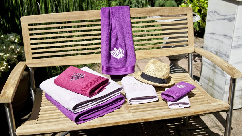 naturel houten schommelbank met roze handdoeken
