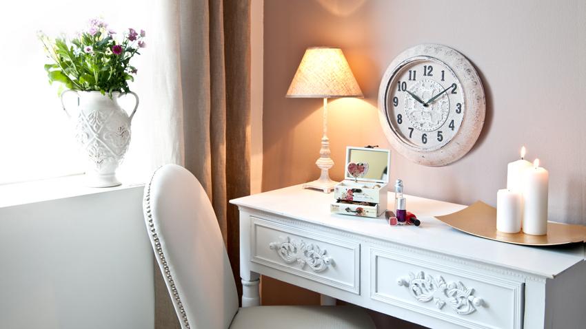 vintage wandklok op roze muur boven schrijftafel