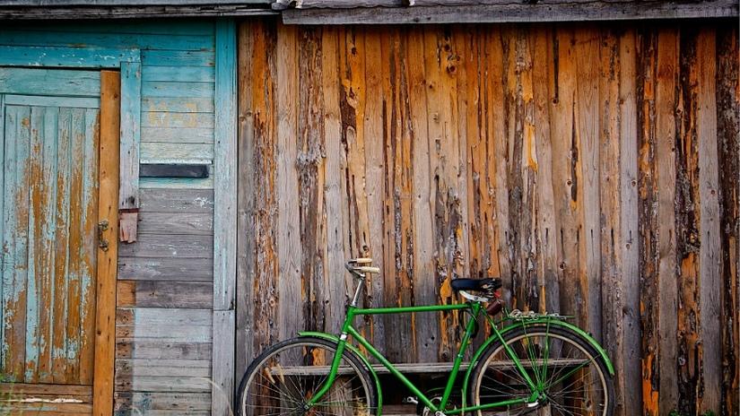 fietsaccessoires kind groene fiets tegen houten muur