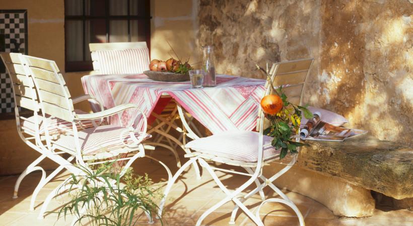 meble ogrodowe, w tym stół ogrodowy i krzesła ogrodowe, stół starannie przykryty obrusem