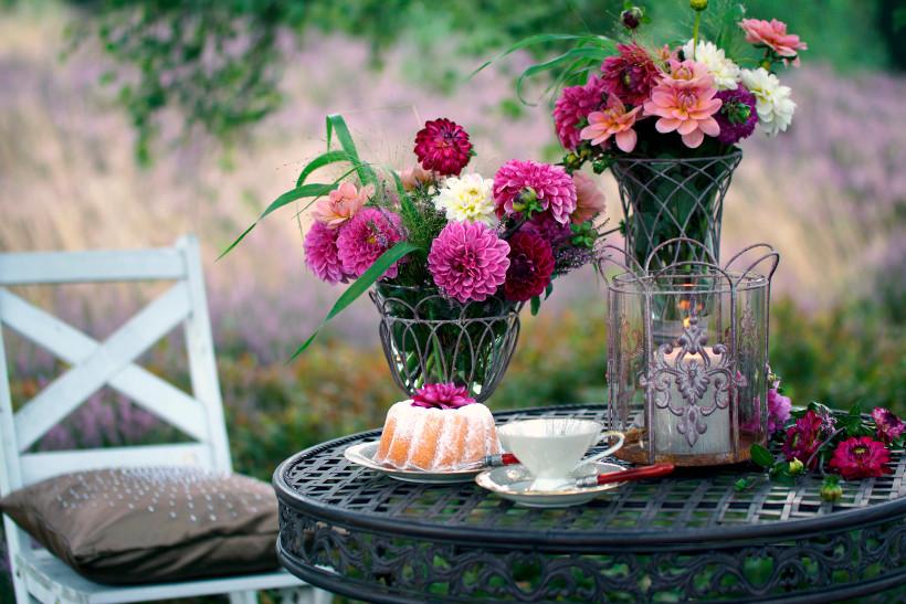 metalowy stół ogrodowy, na którym stoją bukiety kwiatów