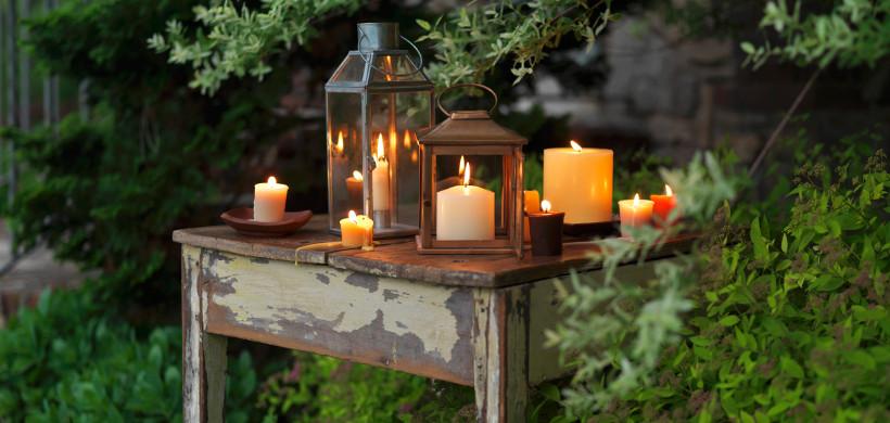 lampiony ogrodowe drewniane z zapalonymi świeczkami