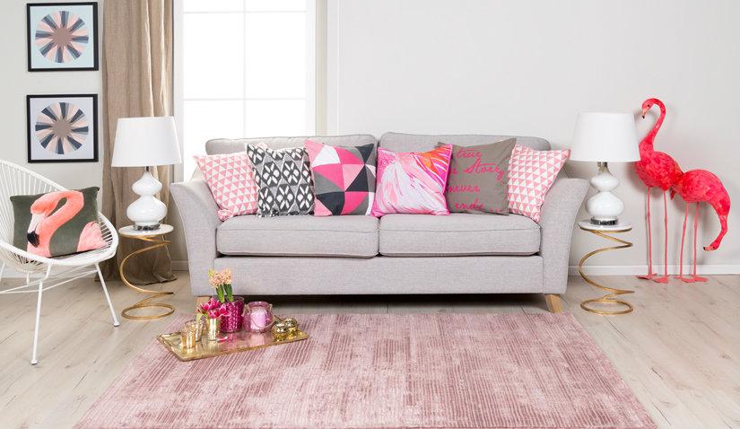 Różowy dywan w szarym salonie