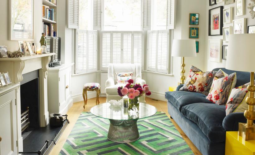 sofa amerykanka ustawiona w malutkim pokoju obita welurową tkaniną wpadającą w szarość