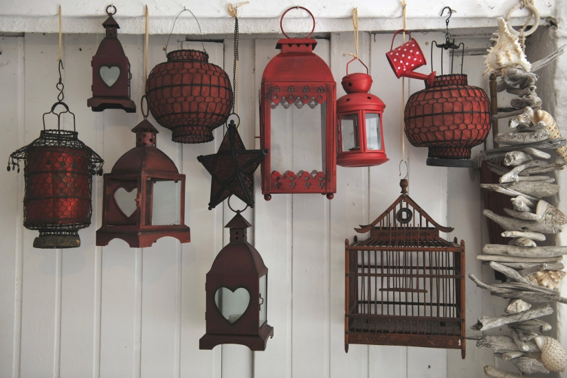 Lanterns of various styles hanging in front of a white wooden wall