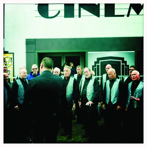 A barber shop quartet outside of the high street cinema