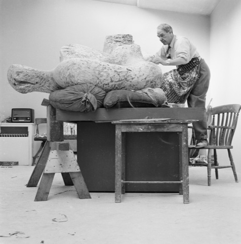 Henry Moore in his studio working on a plaster sculpture, 1960