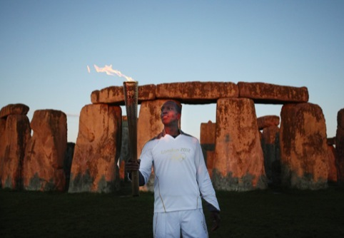 Olympic gold medalist former sprinter Torchbearer 001 Michael Johnson holds the Olympic Flame at Stonehenge at the beginning of Day 55 of the London 2012 Olympic Torch Relay