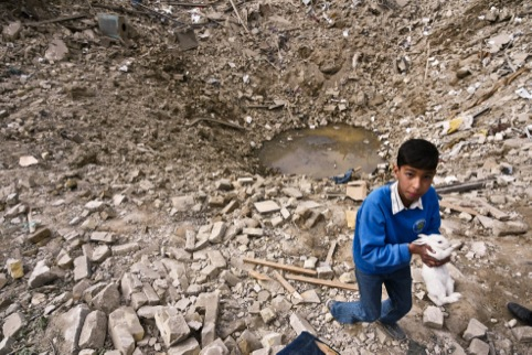 A child recovers a pet rabbit from his bombed neighbourhood, Baghdad, 2003.