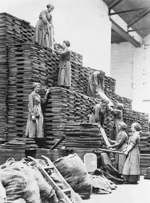 Women workers stacking oil cakes at an Oil and Cake factory, Lancashire, 1918