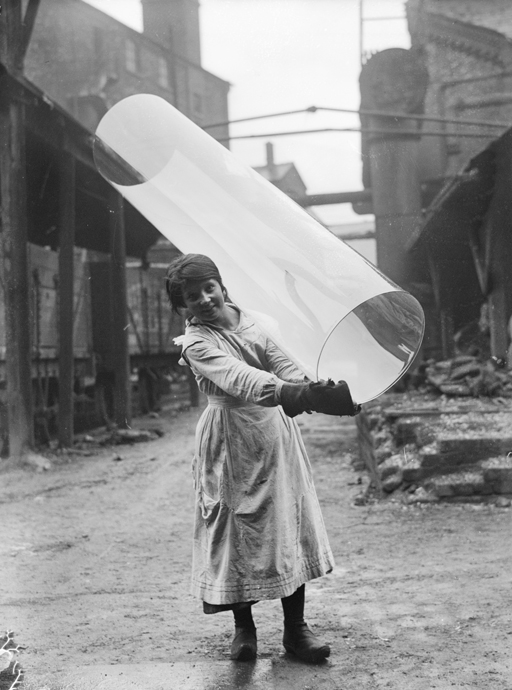 Female glass worker carrying a tube of rolled glass at Pilkington Glass Ltd., St Helen's, 1918. The company still exists today