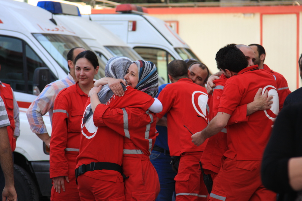 Syria: Humanity in Conflict at IWM North. SARC volunteers returning from a dangerous mission greet their friends outside the SARC centre in Zahira, Damascus, 25 April 2012. The group was trapped in Douma in rural Damascus for 12 hours due to violent clash