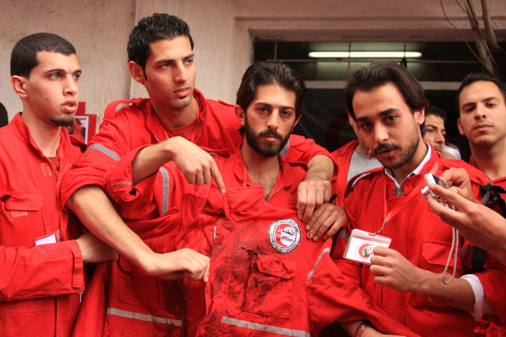 Syria: Humanity in Conflict at IWM North. SARC volunteers hold up the jacket of Mohammad Al-Khadra, a SARC volunteer who died on the 24 April 2013, while on duty in an ambulance on an emergency call. 30 April 2012.