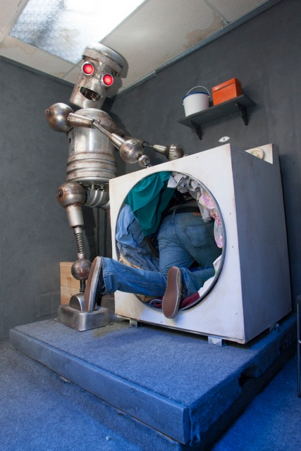 A man crawls though a washing machine as a robot looks on