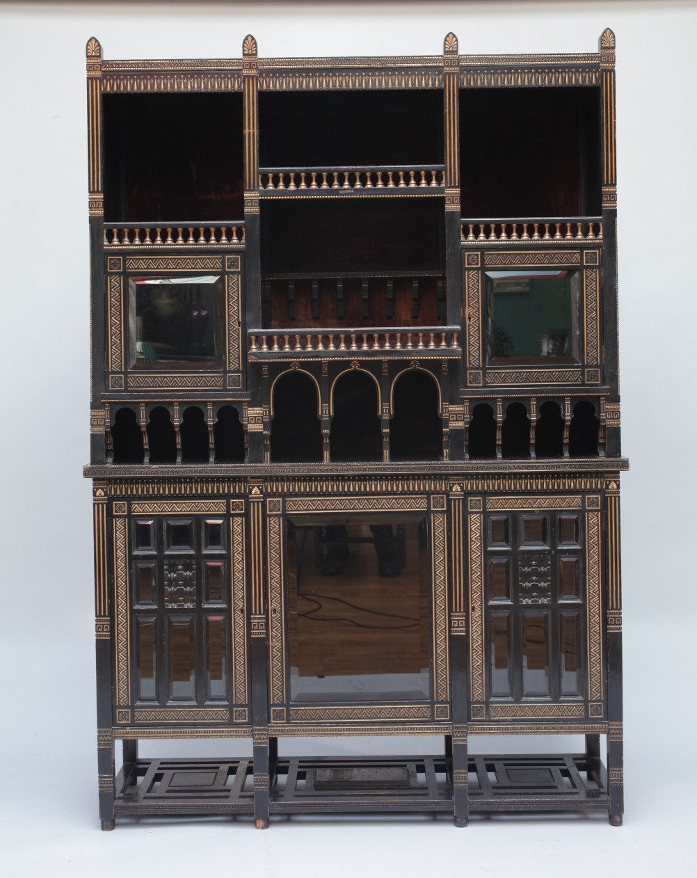 Christopher Dresser (1834-1904) Cabinet, c. 1875. Ebonised and gilded mahogany, glazed doors, with metal disc impressed W. Booty