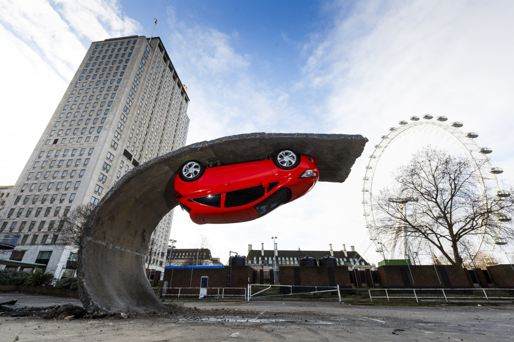 Alex Chinneck, who last year created the Floating Covent Garden in London, has today unveiled this installation in the Hungerford Car Park at the Southbank Centre; a 15ft high, 15 metre long gravity defying sculpture in the shadow of the London Eye where a parking space has peeled back from the ground leaving a new Vauxhall Corsa parked upside down.