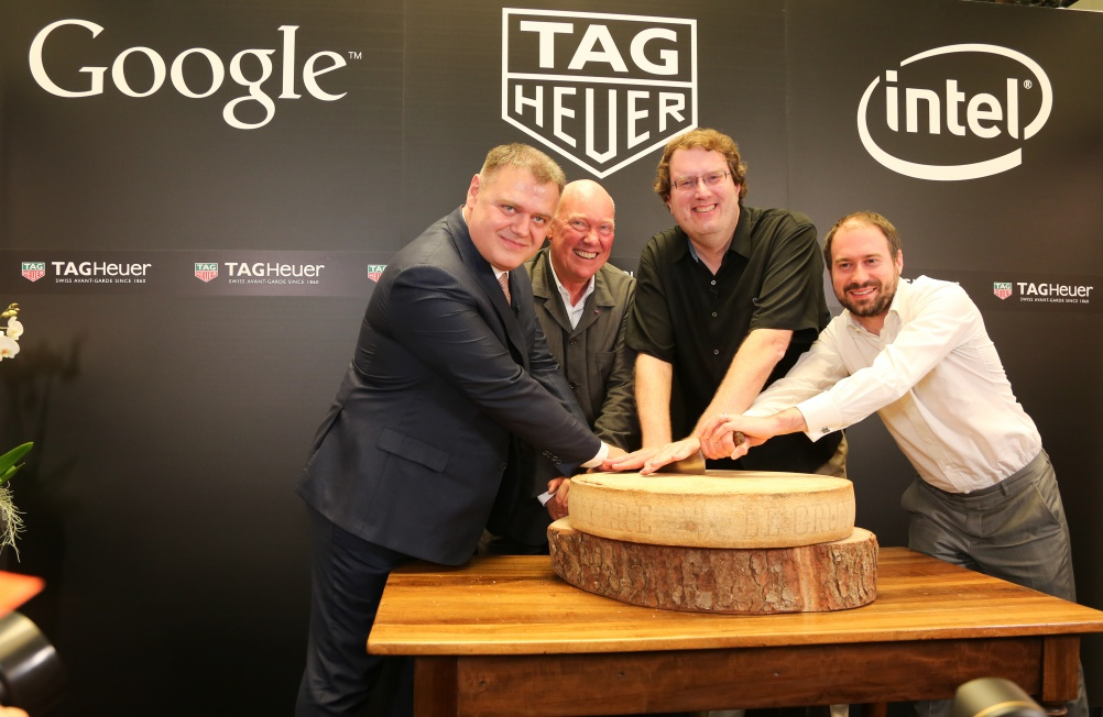 Representatives from Google, Tag Heuer and Intel cut into a large cheese to celebrate their partnership