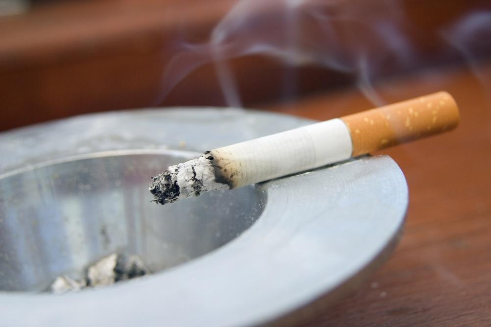 Burning cigarette smoking on ashtray