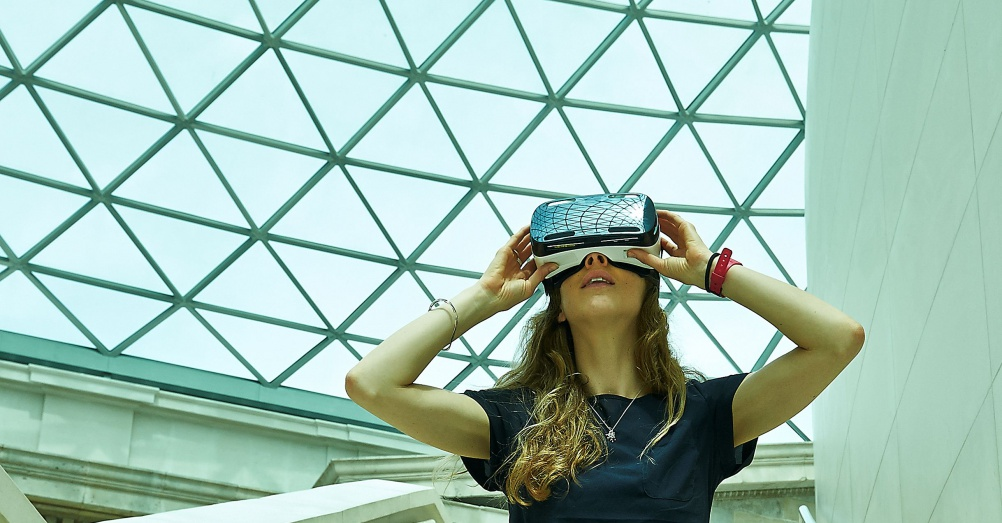 (i) Model wears a Samsung Gear VR headset in the British Museum's Great Court. © The Trustees of the British Museum