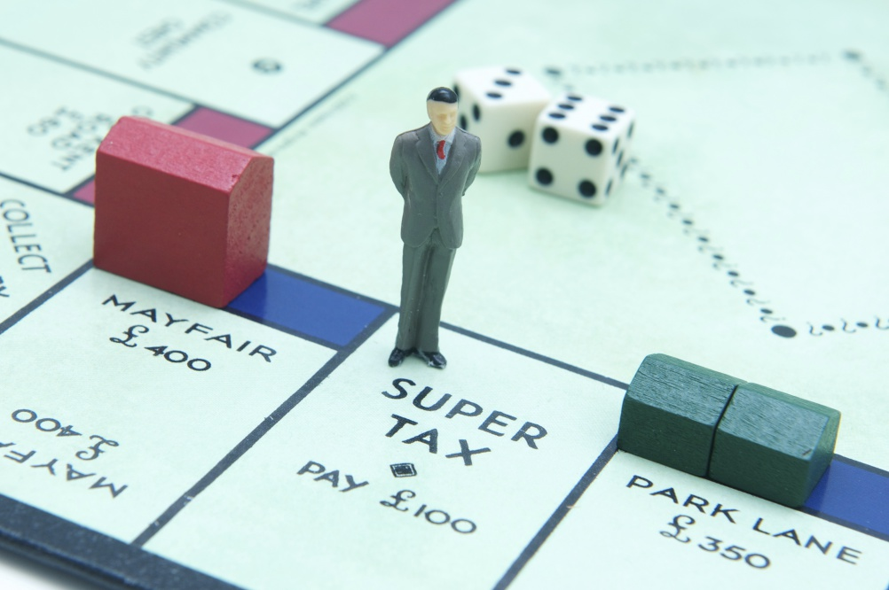 London, UK - July 2, 2011: Model figurine of a businesman standing at Super Tax on the board game monopoly Model figurine of a businesman standing at Super Tax on the board game monopoly with hotel on Mayfair and houses on Park Lane and Dice in the background
