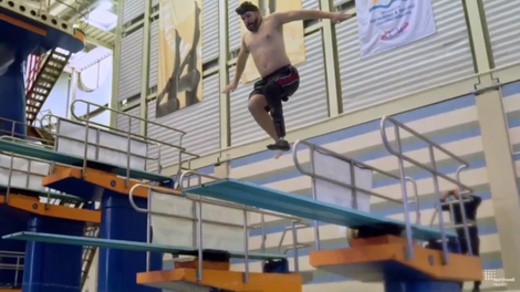 Dan Lasko, a man with an amphibious prosthetic limb, jumps off a diving board into a swimming pool.