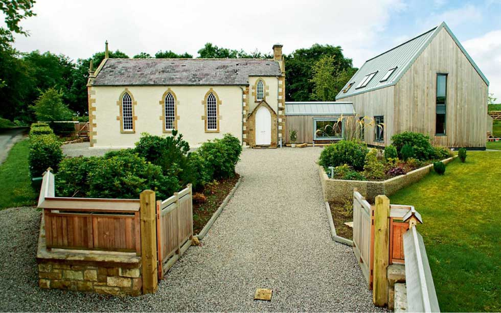 A converted stone church with a timber clad extension