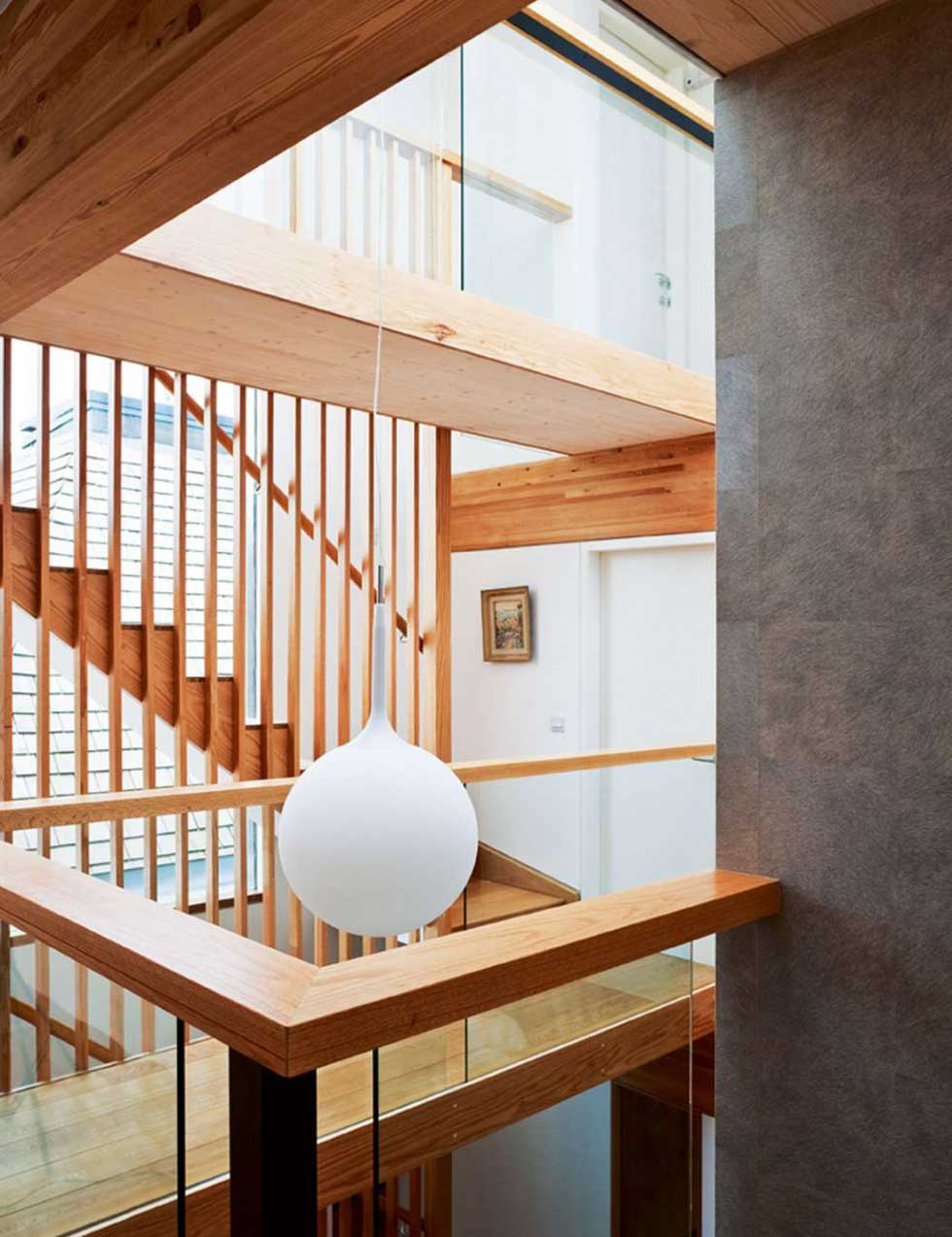 The striking oak staircase was crafted by Cambridge Joinery, with a tall louvred baluster running through all three storeys — creating an internal brise soleil
