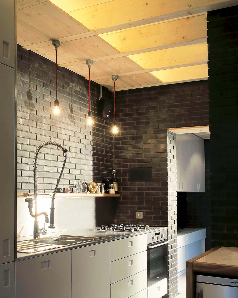 loft style kitchen with untreated wood, exposed brick and simple bulb lights
