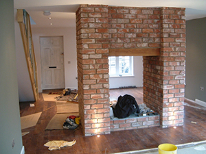 exposed brick feature wall to hold fireplace and fixtures installed