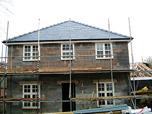 making a house weathertight with windows, finished roof and scaffold