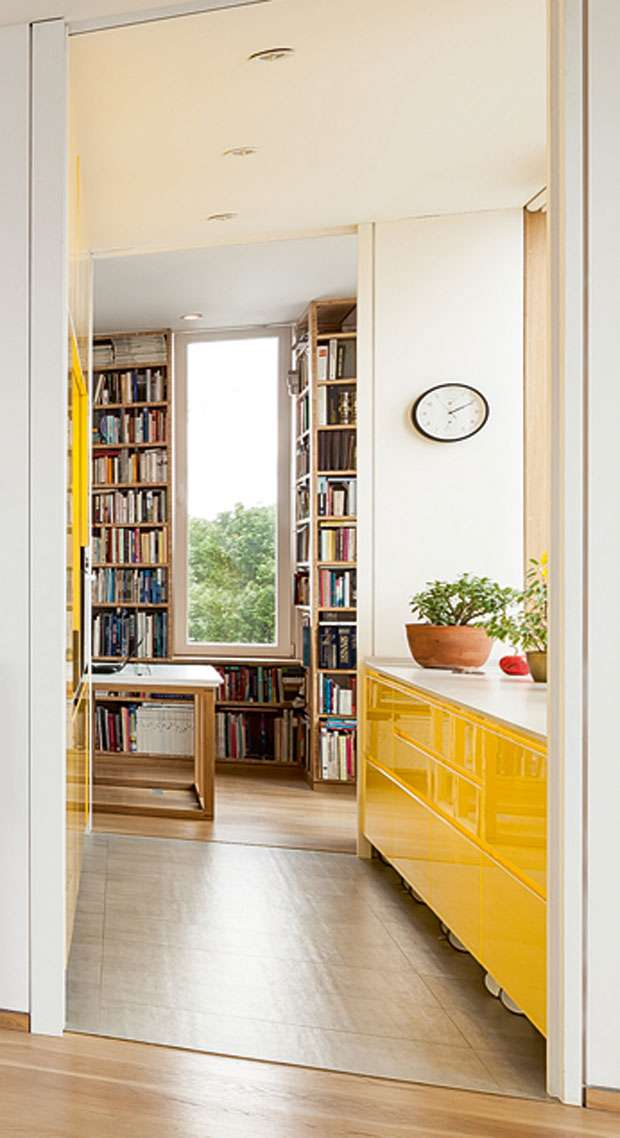 tall picture window surround by books and a reading nook