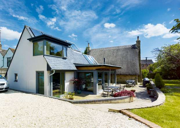 Thatched-with-glazed_side-of-modern-building-and-thatched-house