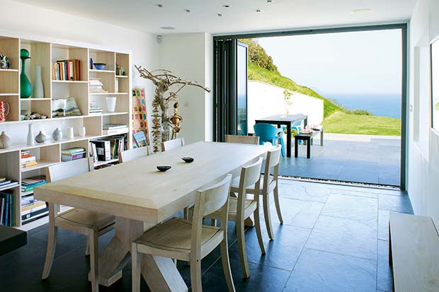 Dining room opening out onto a terrace in a hillside home
