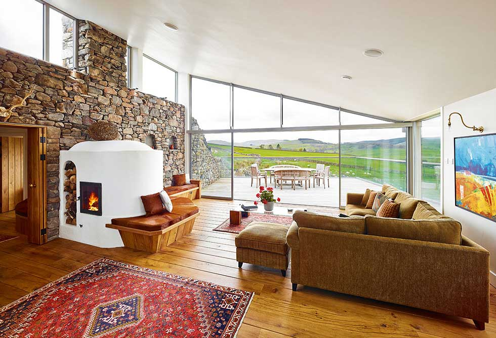 The stove in the main living area heats the dry stone wall that runs through the house