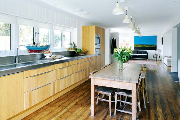 A kitchen in an open plan home with stainless steel worktop and wooden finishes