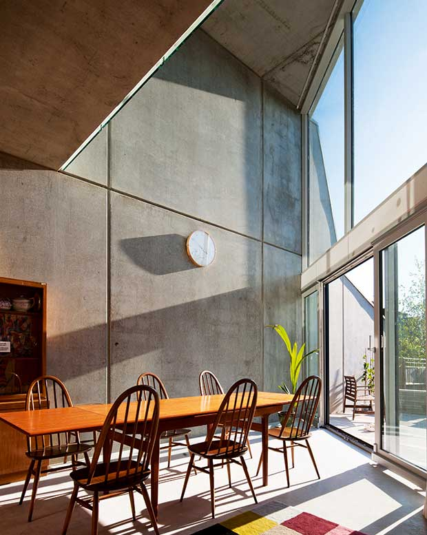 Precast concrete walls in a striking modern dining room with full height glazing