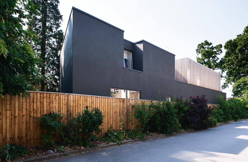 The rear elevation, which faces a private road and a three storey flat development, features minimal windows. A large recess punctuates this elevation at first floor level, enabling a window opening to be introduced, without impeding on privacy.